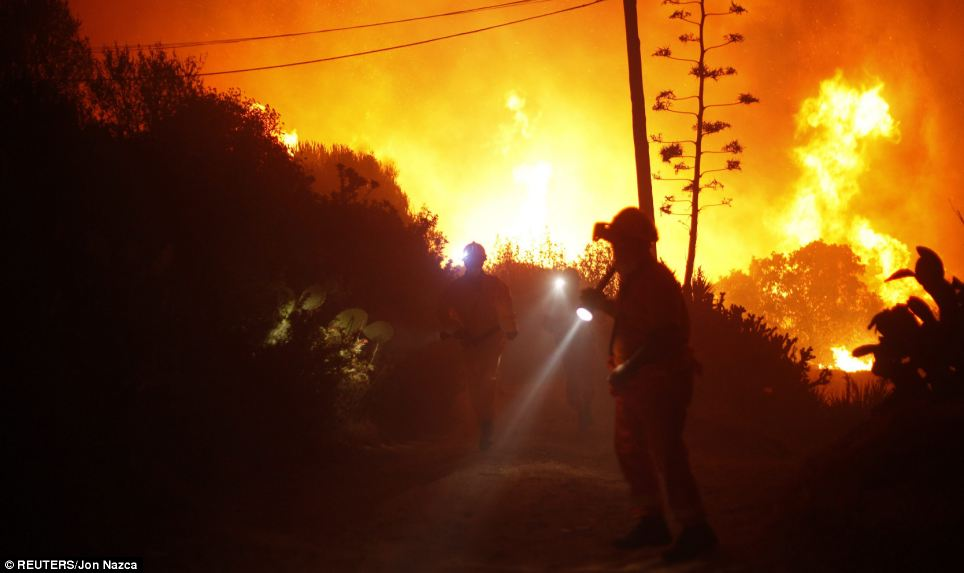 Inferno: Members of Spain's Civil Protection Service search for people trapped as the huge fire rages in Elviria, near Malaga, southern Spain