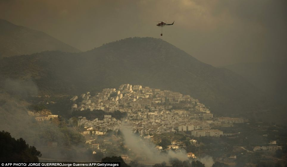 Vulnerable: A fire service helicopter prepares to pour water onto the approaching flames in Ojen