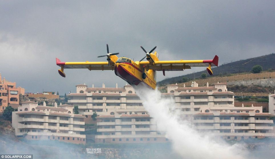 Operation: An aircraft dumps gallons of water on the flames in a bid to stop them reaching nearby buildings