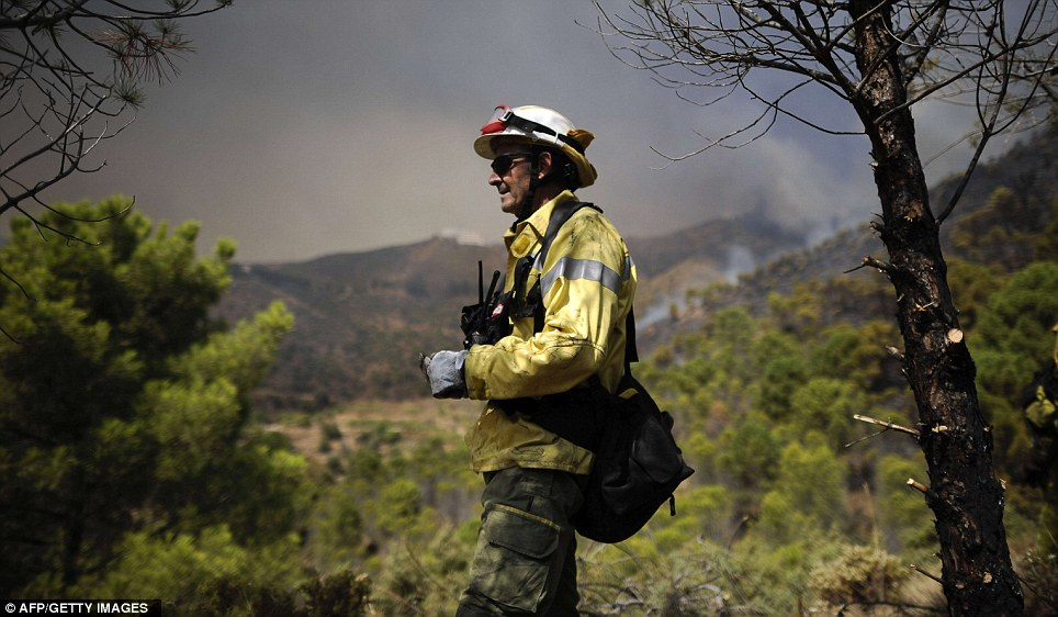 Breather: Firefighter takes a moment as smoke fills the air behind him