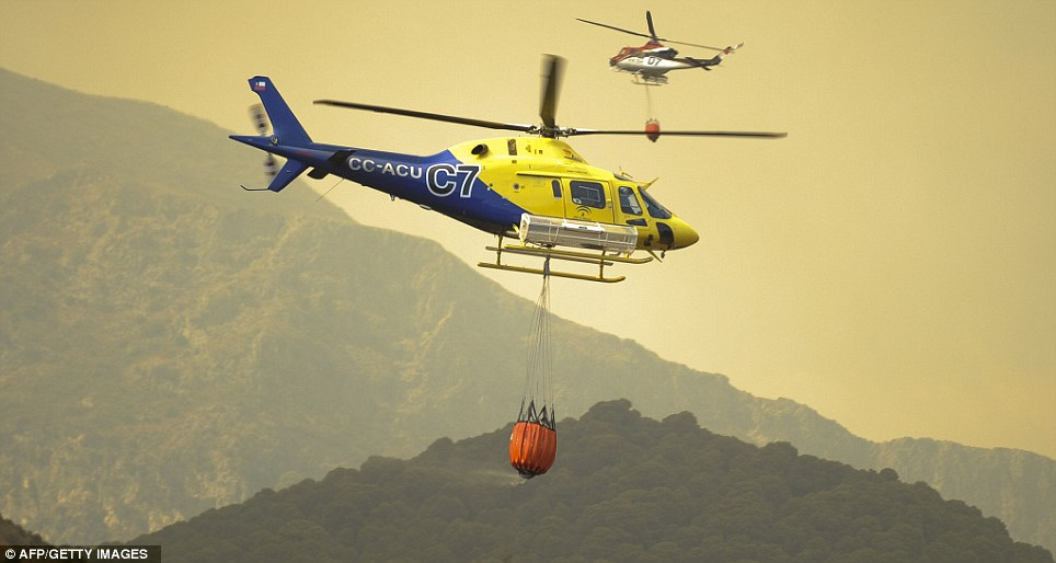 Rescue flight: A helicopter of the Andalucian emergency plan against wildfires (INFOCA) brigade carries water to Ojen