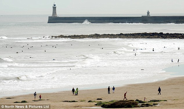 Winter stroll: The scene at Tynemouth Beach looked more like winter than a summer's day