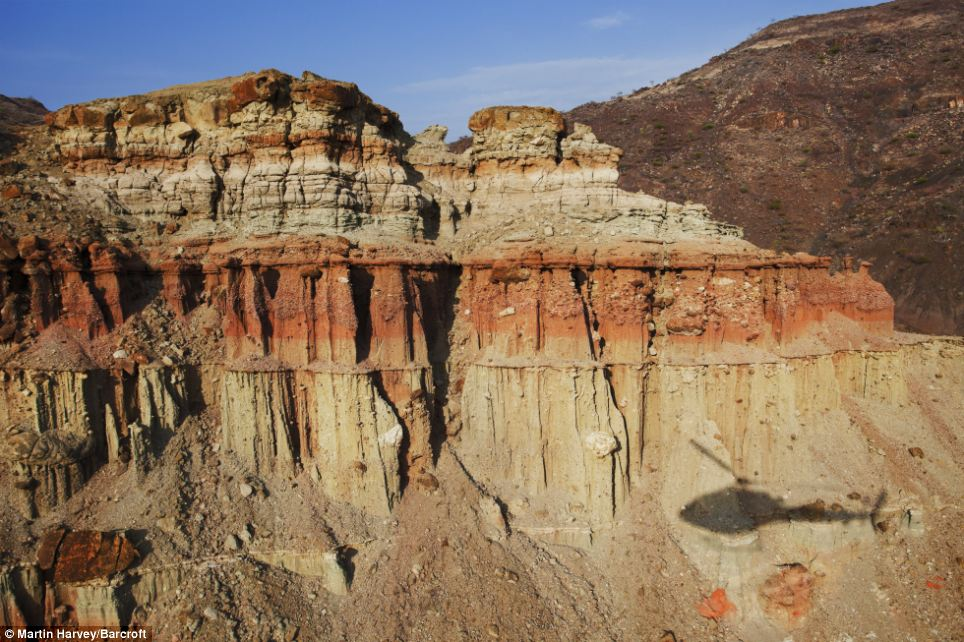 Sweeping views: The shadow of the helicopter can be seen on the rock face as it flies through Painted Valley, within the Suguta Valley
