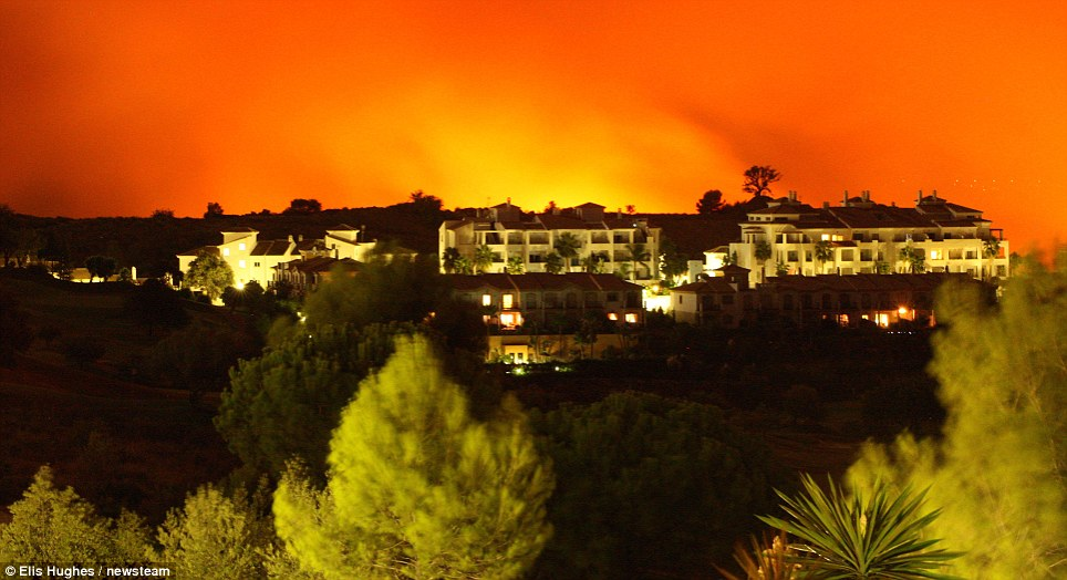 Flaming threat: An eerie orange glow lights up the Spanish sky as the wildfires surrounding Marbella close on the holiday homes of Britons who have been evacuated