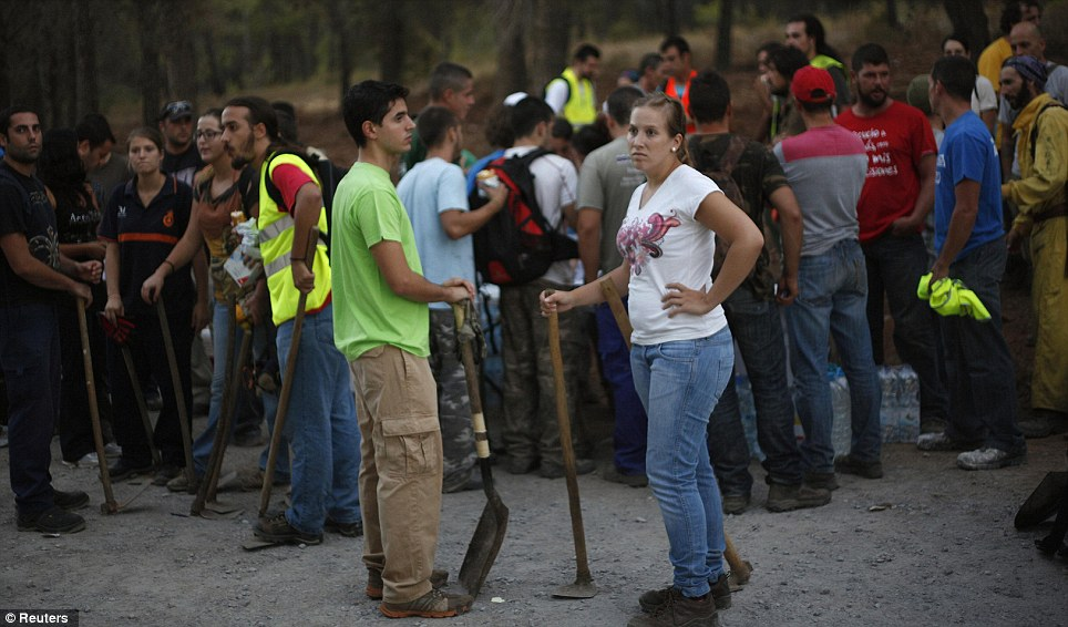 Ready for action: Volunteers wait for orders to guard and clean a burnt out area after a forest fire at Barranco Blanco in Coin where officials believe the original fire started
