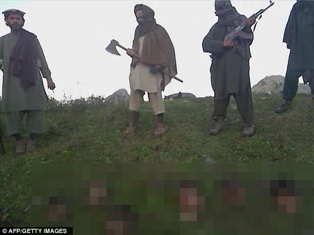 Horrendous: Taliban militants stand over a dozen decapitated heads which they claim belong to soldiers they killed in clashes on the Pakistan border