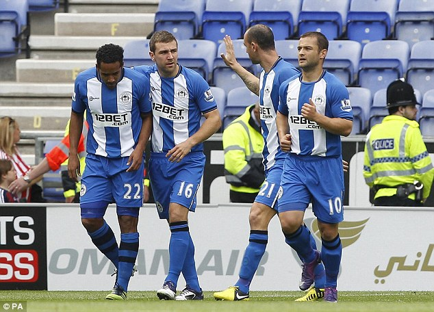 Off the mark: Wigan celebrate after Shaun Maloney's (right) goal