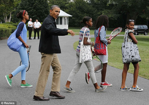 Loving dad: Obama, pictured with his daughters, Malia, left, and Sasha, far right, helps with homework at the White House