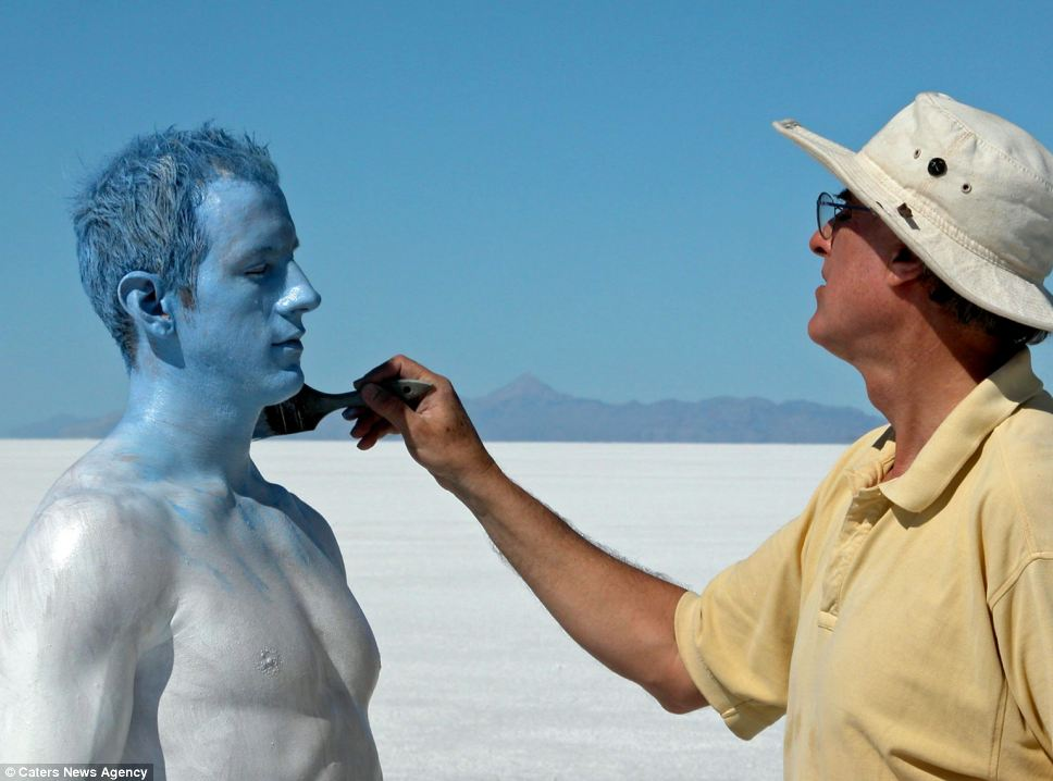 The professor daubs his model in blue paint to match the sky