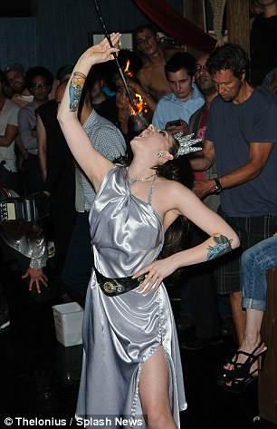 Lady Liberty: Katrina Darling poses as the Statue of Liberty before eating the flame as part of her burlesque act