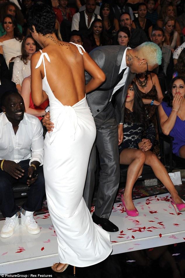 Still close: Chris held onto Rihanna's waist as she stood talking to singer Akon
