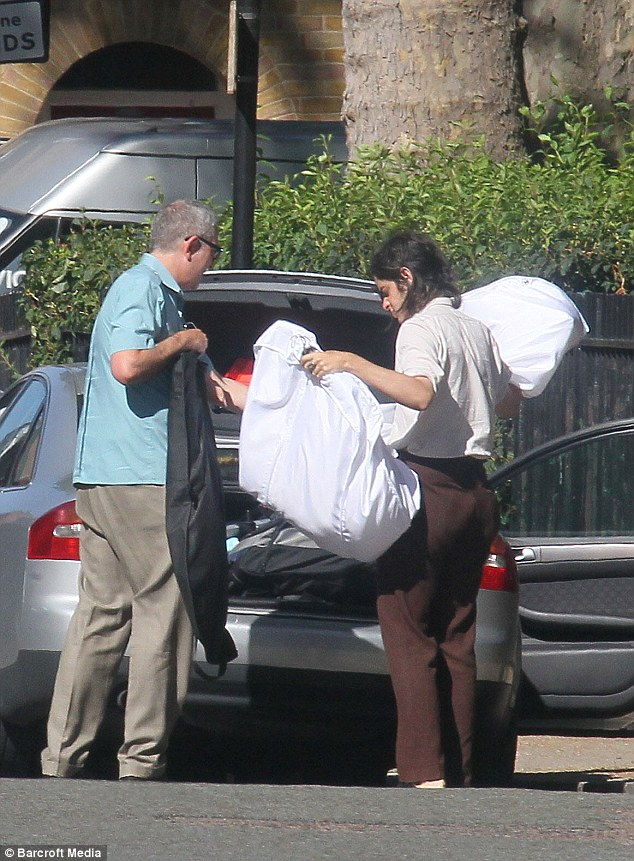 Handle with care: A car is loaded with several garments, including one large dress bag