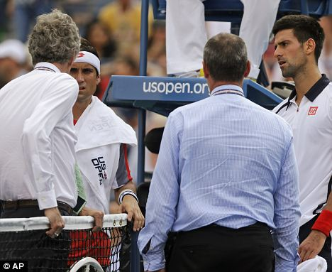 Forced off: David Ferrer, second from left, and Serbia's Novak Djokovic, far right, talk with officials