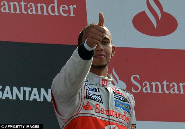 Thumbs up: Hamilton celebrates on the podium