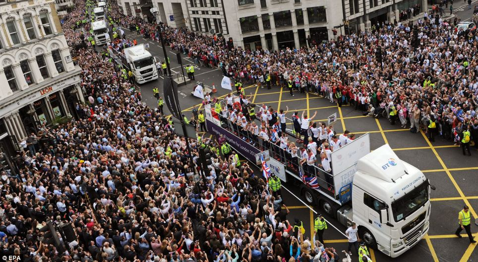 Patriotic: Thousands of Londoners turn out to cheer on Olympic and Paralympic athletes as they travel on floats during 'Our Greatest Team' parade