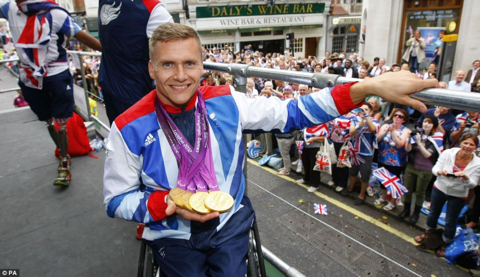Well-deserved applause: Quadruple gold medal winning Paralympian David Weir shows his medals on top of a float