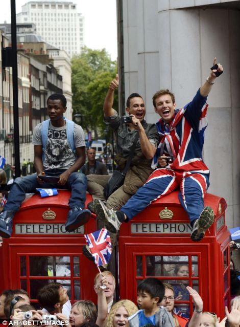 Members of the public wave to the athletes from the top of phone boxes