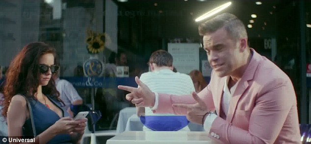 Candy girl: Kaya Scodelario is the object of Robbie Williams' affections in the new video