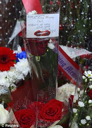 Joy and pain: Steve Kelly of the Hillsborough Justice Campaign with the report (left) and a floral tribute left at Anfield