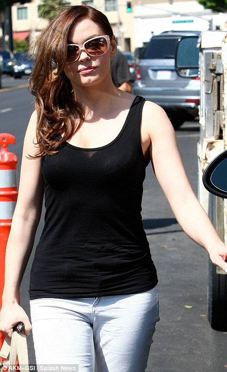 Pretty: With her hair in a bundle of curls, she wore minimal make-up and shielded her eyes with some pink sunglasses