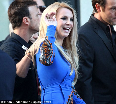 Hi there! Britney Spears waves to fans as she arrives at the X Factor premiere in Los Angeles last night; her team have removed her from any temptation by banning alcohol backstage at the show