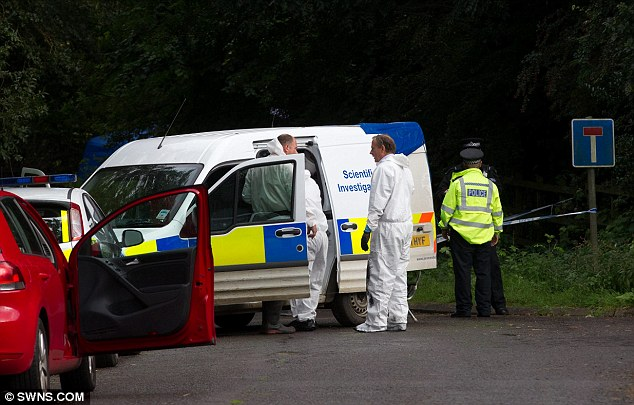 Murder inquiry: Police forensic officers, pictured in white overalls, investigate the scene of the killing