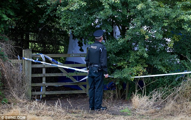 Sealed off: A policeman guards a white tent erected by forensic officers at the site where Ms Wells-Burr's body was discovered