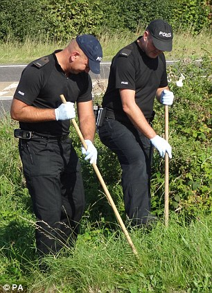 Looking for evidence: Police search for clues close to the scene where Catherine Wells-Burr's body was found in a burning car