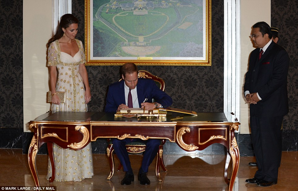 Guests of honour: The Duke and Duchess of Cambridge sign a visitors book before entering the Istana Negara, in Kuala Lumpur