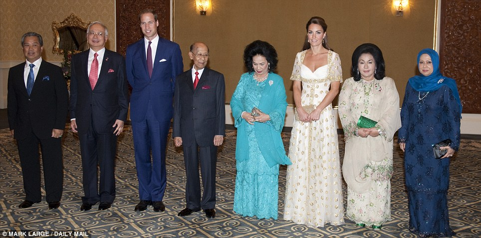 VIP line-up: The Royal couple stood out because they towered over their Malaysian hosts. Kate's exquisitely embroidered white Alexander McQueen dress featured the Malaysian flower, hibiscus, in gold detail