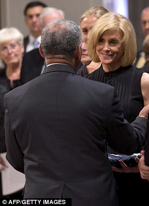 Carol Armstrong, the wife of Apollo 11 astronaut Neil Armstrong, is presented with a flag by NASA administrator Charles Bolden