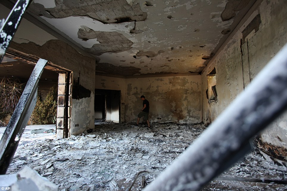 Inhospitable: A Libyan man walks in the rubble of the damaged  building after a crowd of hundreds attacked the consulate Tuesday evening, many of them firing machine-guns and rocket-propelled grenades
