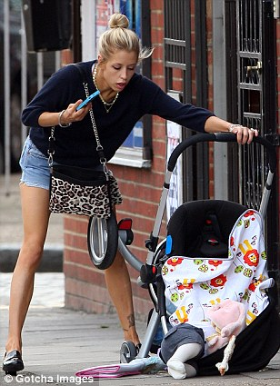 Over he goes: Astala lies half out of the pram, but Peaches still has her phone