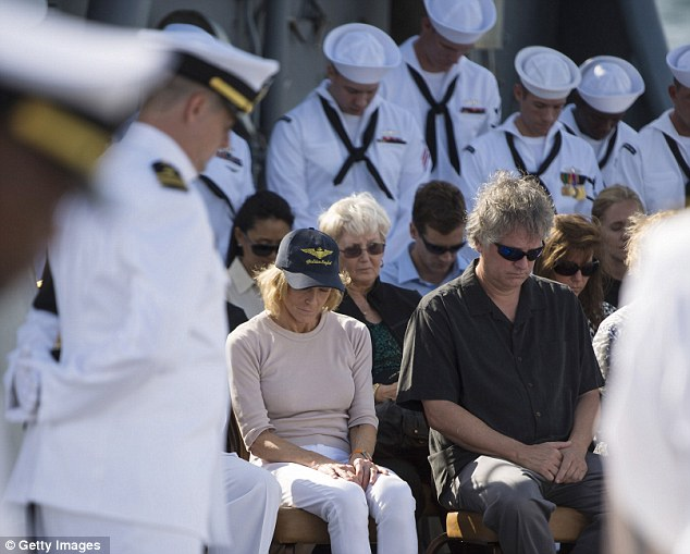 Solemn moments: Carol Armstrong, second left, wife, and Eric 'Rick' Armstrong, son of Neil Armstrong, right,  bow their heads during Neil Armstrong's burial at sea service