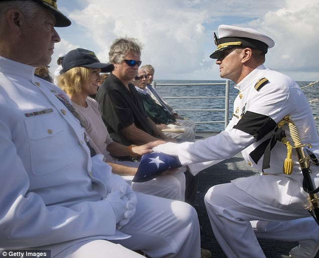 Military burial: U.S. Navy Captain Steve Shinego, commanding officer of the USS Philippine Sea, presents the U.S. flag to Carol Armstrong following the burial at sea