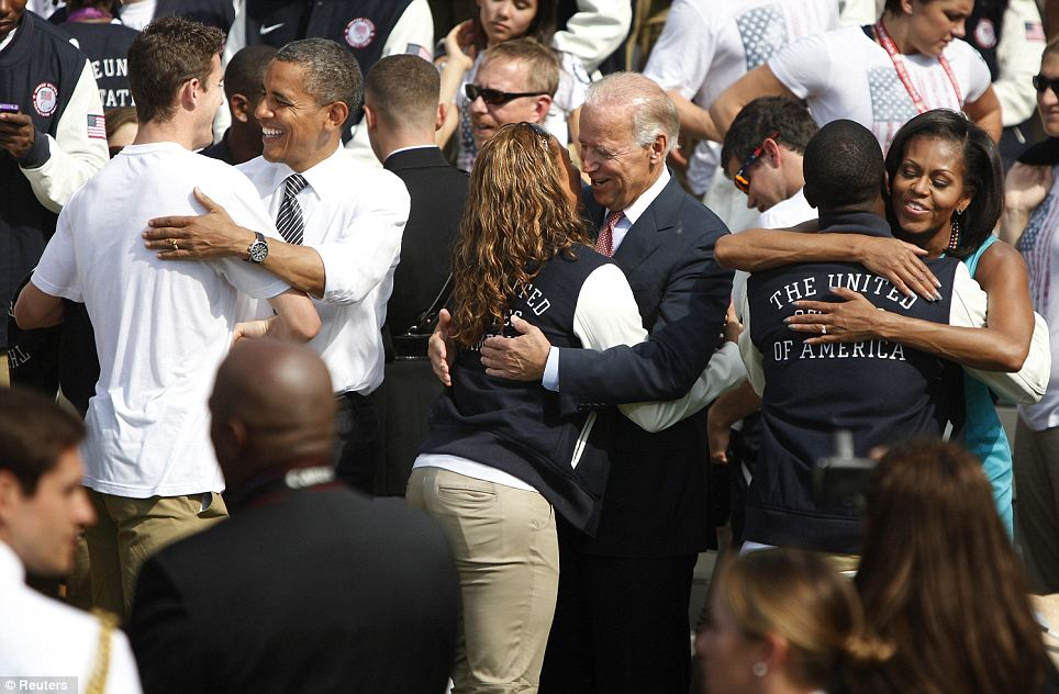 Hugs and kisses: Athletes get up close and personal with the Obamas and Vice President Joe Biden (centre)