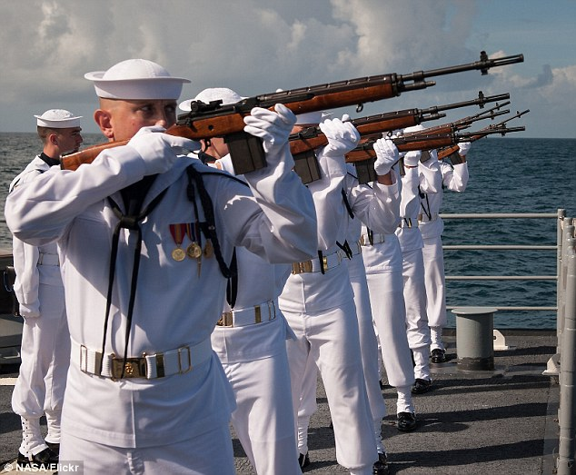 Salute: A US Navy firing squad fires three volleys in honor of the lunar pioneer