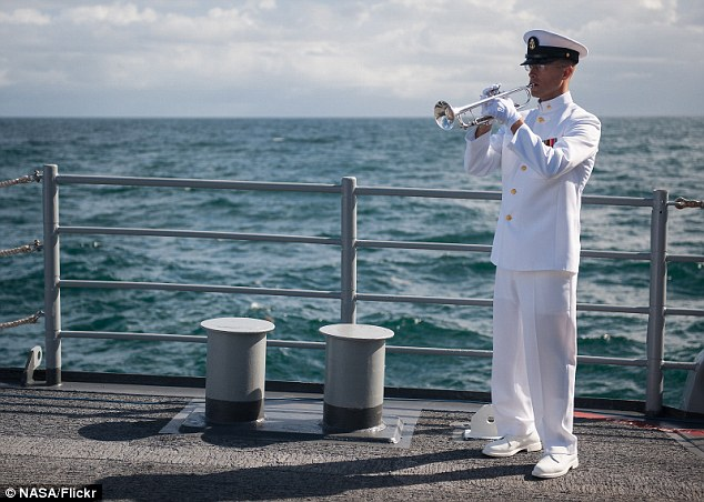 Taps: Chief Musician for the United States Navy Band, Gunnar Bruning, plays Taps on a silver trumpet during the burial at sea