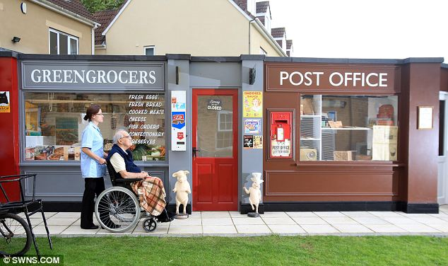 Reliving the past: Arthur Lloyd, an 86-year-old care home resident from Liverpool, is taken down 'Memory Lane', with its authentically decked out greengrocers and Post Office by care assistant Rebecca Stone