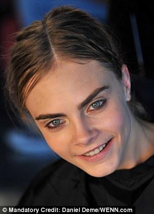 Laidback: Cara Delevingne having her hair done backstage