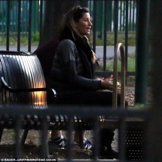 Well-deserved rest: The trio stopped in the park's playground where the doting mother got a chance to rest on a bench as the boys played