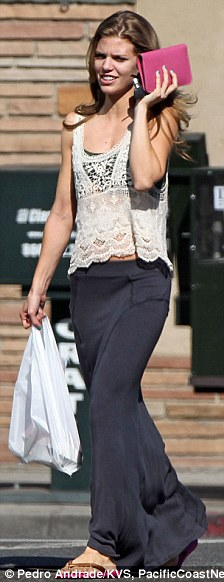 Hiding away: The pretty 25-year-old, dressed in a sheer lace tank top and grey maxi skirt, looked like she was trying to hide her face with her pink wallet