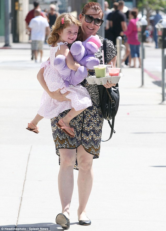 Hands full: Actress Alyson Hannigan with her three-year-old daughter Satyana in Santa Monica today