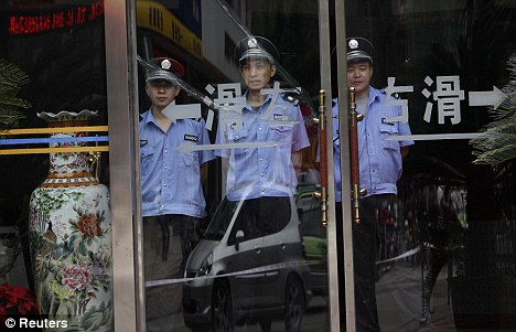 Guards stand in a shop next to the Chengdu Intermediate People's Court where the trial is being held behind closed doors amid tight security