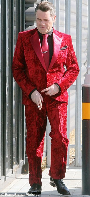 Man in red: Chris wore a red silk patterned suit, teamed with a black shirt and red tie for the role