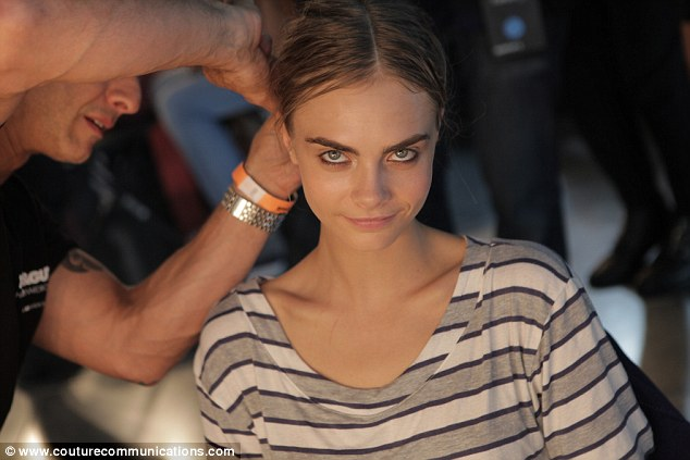 All in day's work: Cara Delevingne smiles between grimaces of pain as Cos Sakkas of Toni & Guy pins her bun to her head