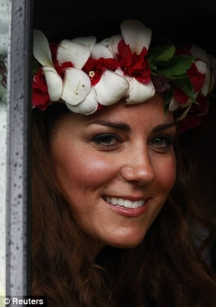 Star attraction: The Duke and Duchess are treated to more energetic song and dance performances from villagers, having given Kate a brightly-coloured decorative headpiece (right)