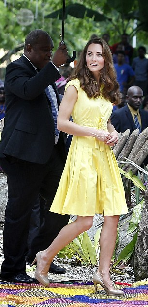 Resplendent in yellow: Dressed in a bright yellow sleeves dress, which cost £180 from Jaeger, and her trusty beige LK Bennett heels, Kate cut a colourful figure as she and William were greeted by fearsome island warriors singing war chants