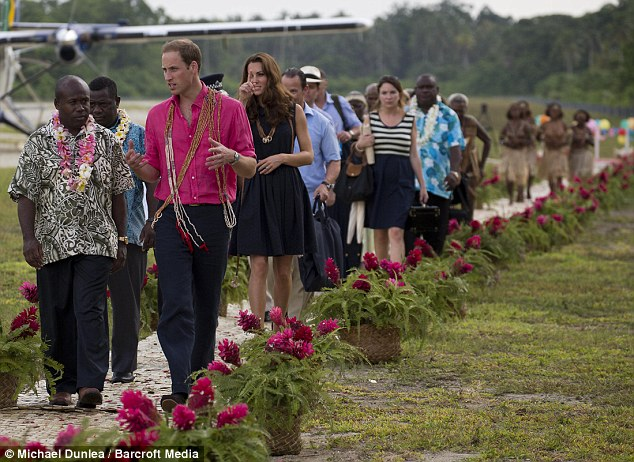 On our way: Prince William chats with an islander as he makes his way through a path of brightly coloured flowers at the Marau landing strip