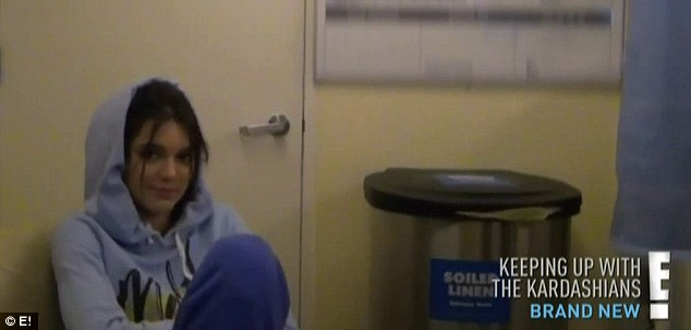 At the sidelines: Kourtney's sister Kylie sat in the corner with a hood over her head